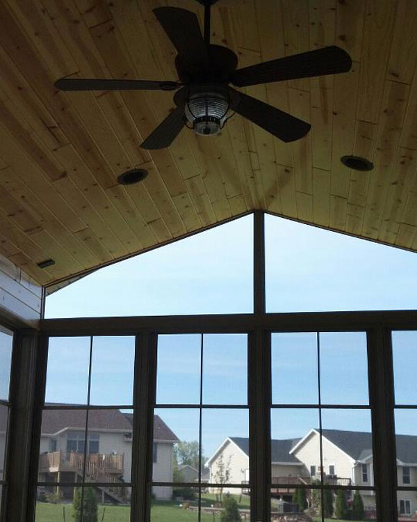 Interior sunroom home addition with hardwood ceiling and wall to wall windows